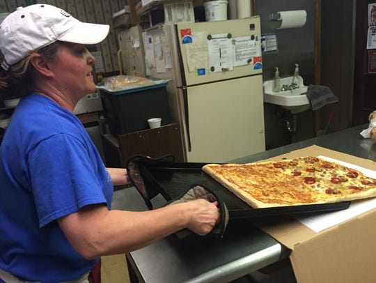 Bill Meade's stepdaughter, Sue O'Neil, flips a pizza