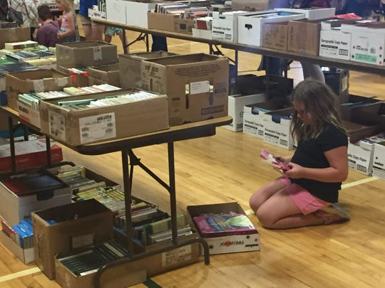 """8-year-old Mya Thibert looks for """"Goosebumps"""" books at the free book giveaway."""