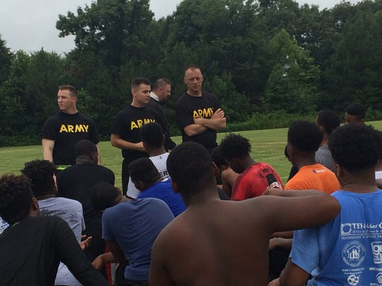 Recruiters from the local National Guard posts talk to Liberty's football players after putting them through a boot camp workout on Thursday.