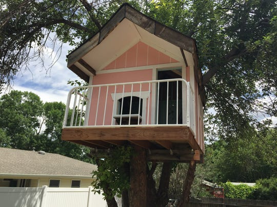 This little treehouse in the Thunderbird East subdivision features an old bed headboard repurposed as a balcony.