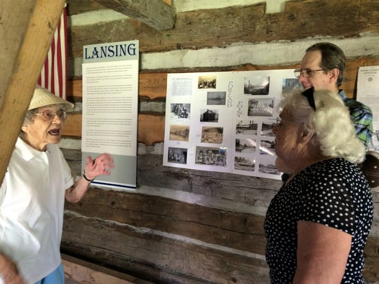 Margaret Listar tells stories of Portland Point to Dick Avery and Fannie Welch. The Lansing Historical Society put on the exhibits in the North Cabin in Myers Park in honor of the town's bicentennial.