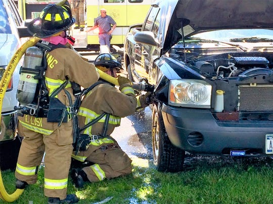 Lansing firefighters pour water into a smoking truck Tuesday afternoon near the marina at Myers Park in Lansing. The firefighters worked for more than an hour to put out the fire.