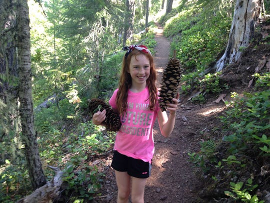 Kelsie Lechleiter holds up a sugar pine cone.