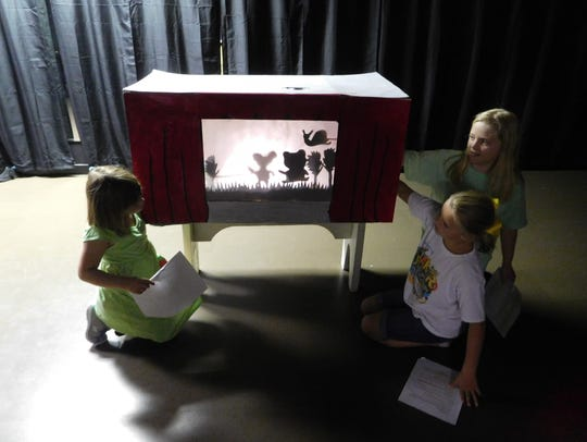 Original scripts in hand, campers put on a shadow puppet