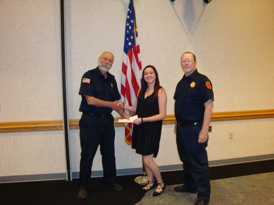 Raritan Valley Community College student Chelsea Castro, center, receives her Somerville Fire Department Fire Police scholarship award for the 2016-17 academic year with Greg Jobin, left, and Kent Buchanan, right, of the Somerville Fire Department Fire Police.