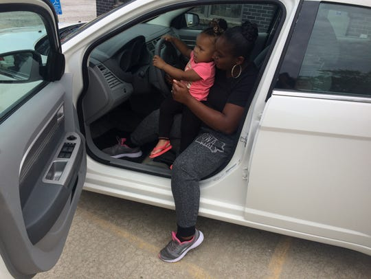 Candis Allen and her daughter check out the car that