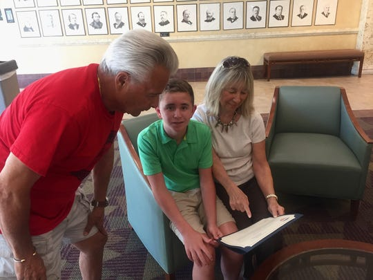 Ryan Baudo and his grandparents, Connie and Frank, admire the Veterans Council appreciation certificate.