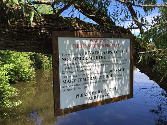 A sign over Scuppernong Creek where it enters  Upper