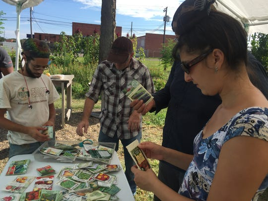 Gardeners Tevin Gray (from left), Matt Hanson and Shirin Delsooz look through packets of seeds on the table at Grow Local's Seed Swap on Sunday, July 16, 2017.