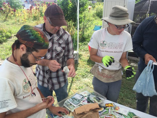 Gardeners Tevin Gray (from left), Matt Hansonand Michelle Kish look through packets of seeds on the table at Grow Local's Seed Swap on Sunday, July 16, 2017.