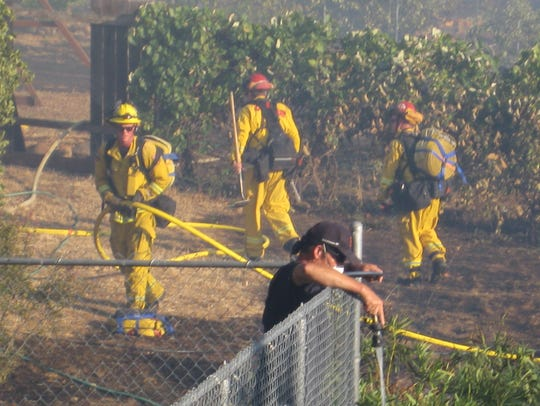 A resident and Redding firefighters help fight a fire