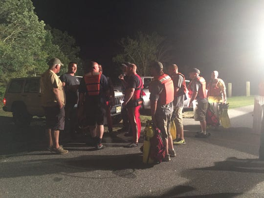 Downe Township Dive Team members talk with investigators and firefighters as they prepare to recover two bodies from South Vineland Park Lake Wednesday night.