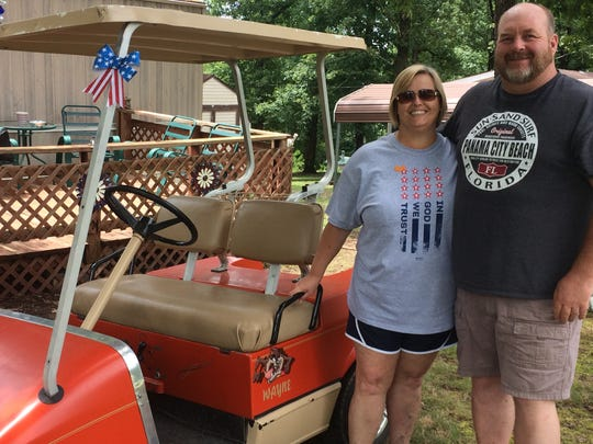 Donna and Wayne Groves with their golf cart.