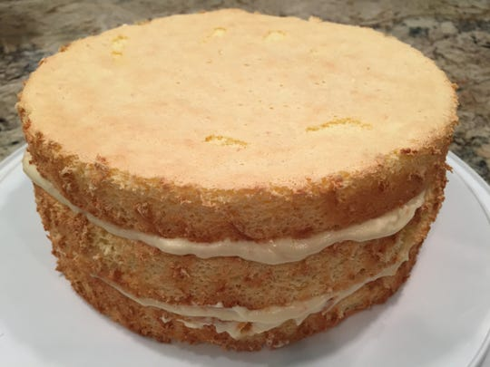 A cooked orange filling blended with whipped cream is spread between the layers before the cake is frosted.
