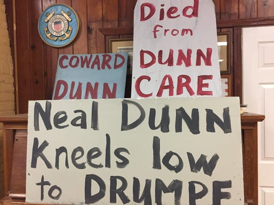 Angered by his vote to repeal the ACA , members of the DCNF brought signs lampooning the Congressman