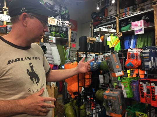Joshua Stephens, camping goods buyer for Outdoor Gear Exchange in Burlington, shows the variety of bug repellent products the store sells on Monday, July 24, 2017.