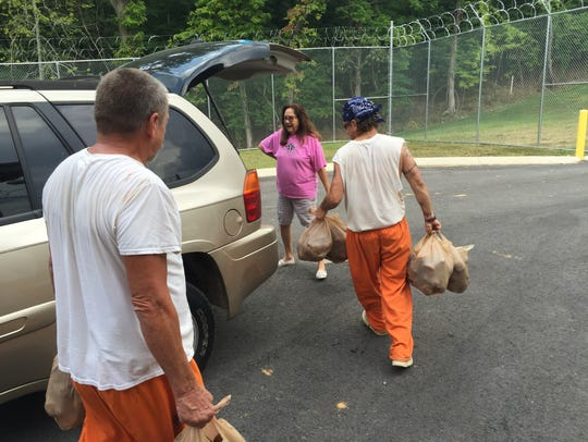 Stewart County jail inmates carry several bags of potatoes