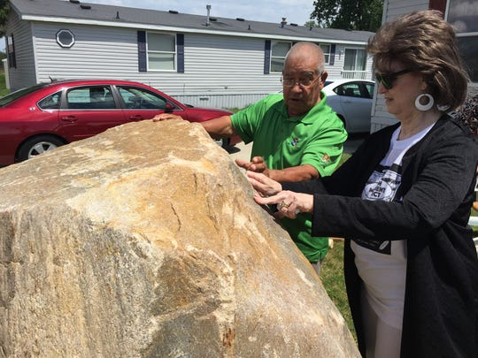 Trish Moss helps John Kennedy as he starts to carve words into a large rock that will become a monument to Native Americans.