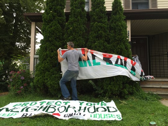 James Murphy ties a banner to Elizabeth McGriff's home. She is threatened with eviction.