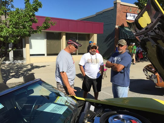 Bill Shaw, left, of Brights Grove, Ontario; Hector Sein, of Port Huron; and Reese Sein, of St. Clair, talk about Shaw's 1974 Corvette convertible at the Mainstreet Memories Car Show.