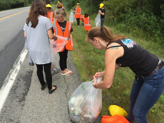 Debbie Wheeler helps the Dover cheerleaders with roadside cleanup on July 29.