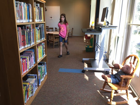 Mackenzie Kovacs, 11, daughter of Loretta and Jeffery Kovacs, checks out the new children's section of expanded, renovated Shippensburg Library Monday, July 31.