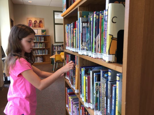 Mackenzie Kocacs, 11, checks out books available in the new children's wing of Shippensburg Public LIbrary, on July 31, 2017.