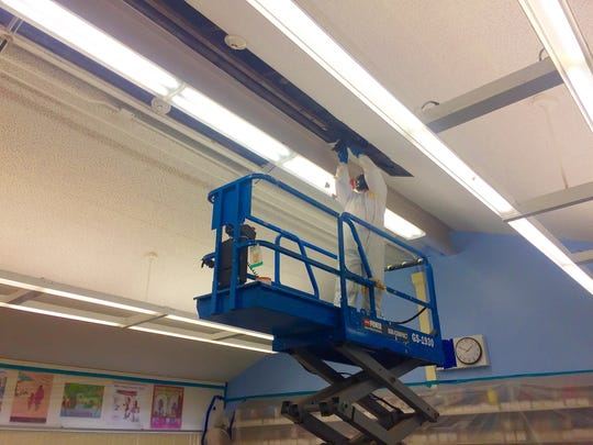 Juan Servein works on removal of possible mold from ceiling tiles.