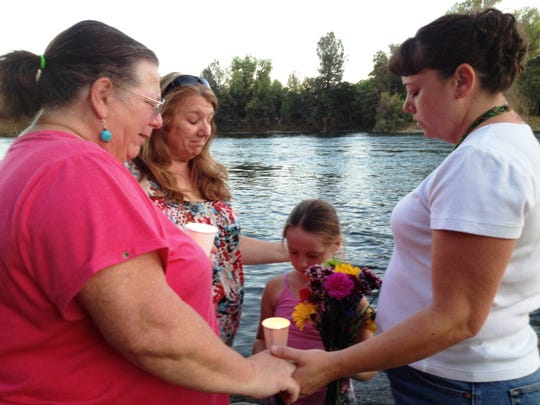 Sandra Dietrich (from right), her daughter Kiaya, Lee Ann Lawrence and Sheryl Miller held a candlelight vigil in August 2014 for Dietrich's son, Cort Jones-Botta, who has been missing for two years.