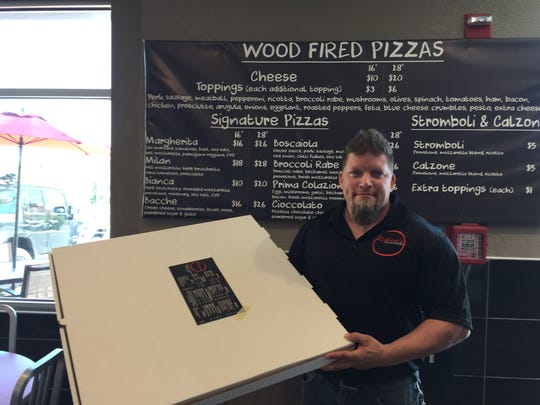 Ripieno's owner Kirby DiSeveria holds the 28-inch pizza box in front of the pizza menu at his business at 33rd and Coastal Highway in Ocean City.