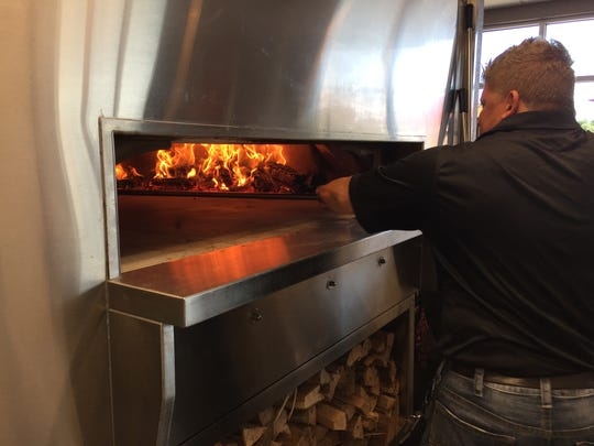 Ripieno's owner Kirby DiSeveria works the wood-fire oven at his business in Ocean City