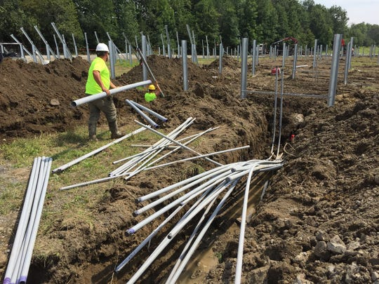 Construction crews with Bullrock Corp. of Shelburne work at the site of a solar project at Dreamwalker Farm in Grand Isle on Friday, Aug. 11, 2017.