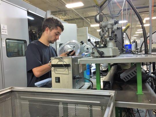 Antonio Danino, 18, examines auto parts for imperfections