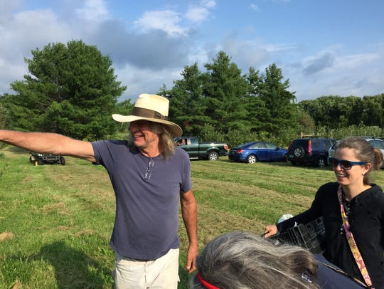 Nick Cowles, owner of Shelburne Orchards, shows visitors