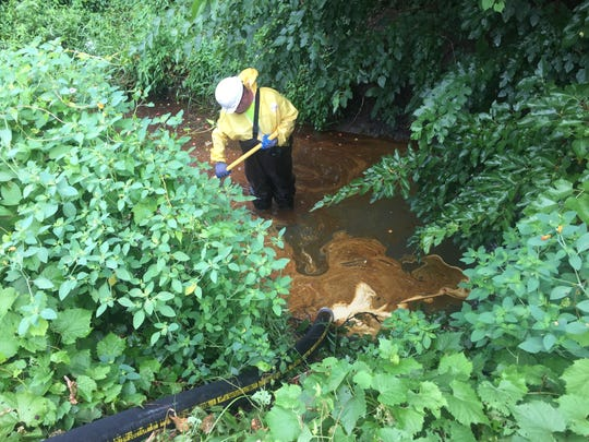 A worker collects hydraulic fluid and oils in the Teske Drain in Clinton Township Aug. 15, 2017 after the fluids got into the drain after a fire at a business in Fraser last week, Macomb County Public Works officials said.