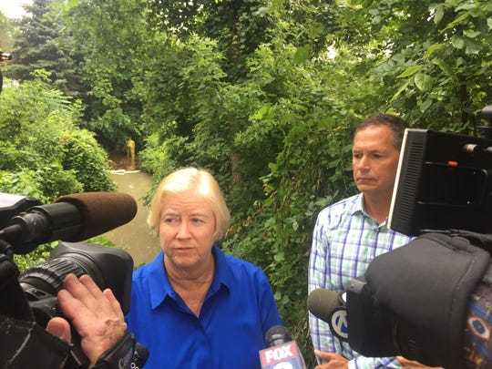 Macomb County Public Works Commissioner Candice Miller and County Commission Chairman Bob Smith address the media Aug. 15, 2017 as a worker behind them collects hydraulic fluid and oils spilled into the Teske Drain in Clinton Township after a recent fire    at a Fraser business.