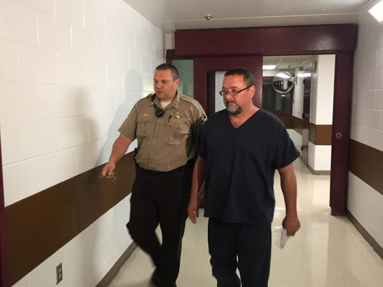Patrick Elliott is led to his initial hearing Tuesday.