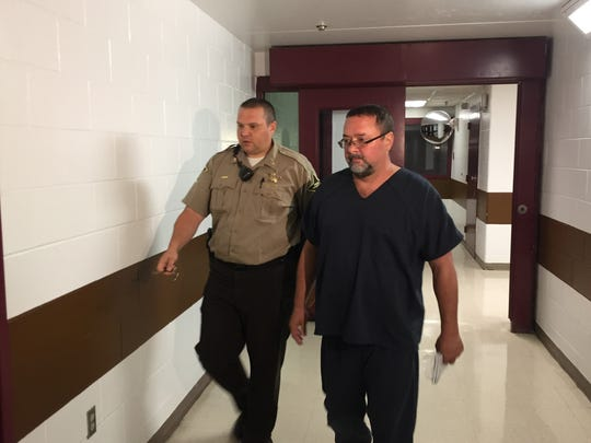 Patrick Elliott is led to his initial hearing Tuesday. Elliott is charged with murder. He is accused of killing his wife, Donita, inside their home on Aug. 8.
