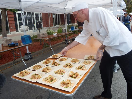 Chef David Burt makes sure the plates are in the right place before food is served at the second annual Farm to Street Dinner in the 100 block of North Linn Street in Iowa City on Aug. 17, 2017.