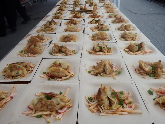 Pork belly dumplings with apple kimchi from Dumpling Darling wait to be served at the second annual Farm to Street Dinner in the 100 block of North Linn Street in Iowa City on Aug. 17, 2017.