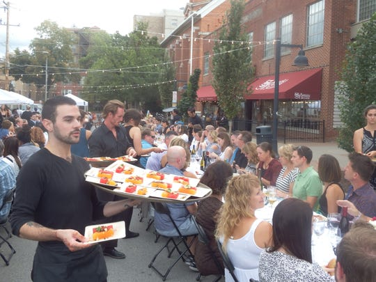 Servers hand out the first course at the Farm to Street Dinner  in the 100 block of North Linn Street in Iowa City on Aug. 17, 2017.