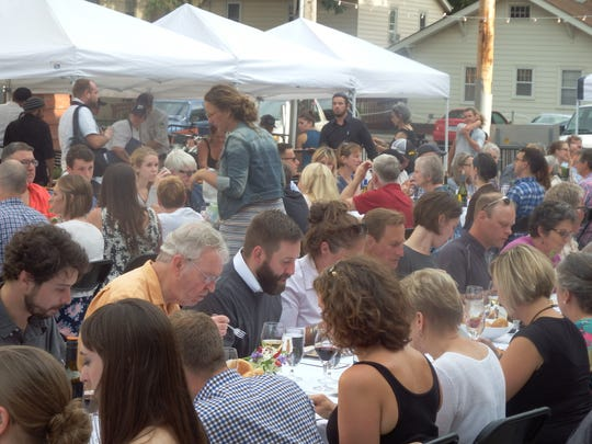 Diners enjoy the first course of the second annual Farm to Street Dinner in the 100 block of North Linn Street in Iowa City on Aug. 17, 2017.