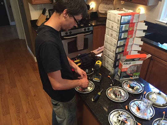 George Gulya, 22, an apprentice with GenRenew, works on an energy-efficient lighting system in Howell.