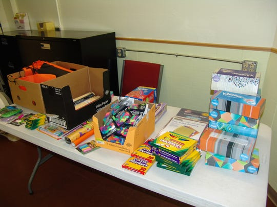 Supplies line a table at New Life Ministries in preparation for the annual school supply giveaway.