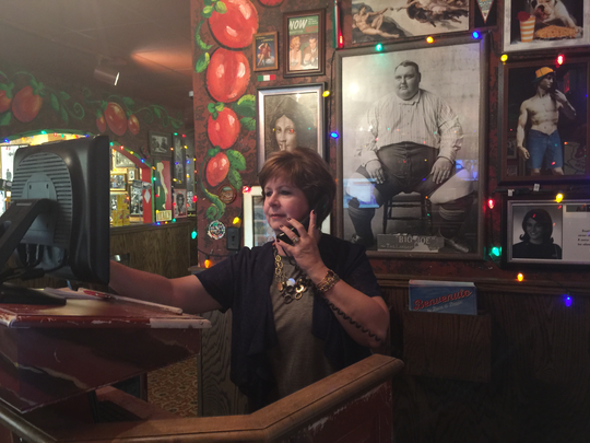 Buca di Beppo manager Lorie Barbian attends to customers in front of a picture of the restaurant's founder, Joe Micatrotto.