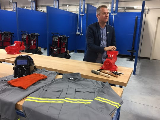 Phenomenal Welding President Stefan Takac shows clothing,
