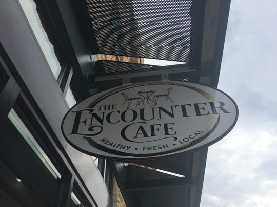 A sign for The Encounter Cafe hangs in front of the business at 376 S. Clinton St. in Iowa City on Aug. 25, 2017.