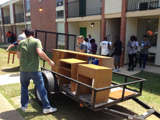 Crews remove old furniture that will be replaced with new items inside a Palmetto North apartment on Friday, Aug. 25, 2017.