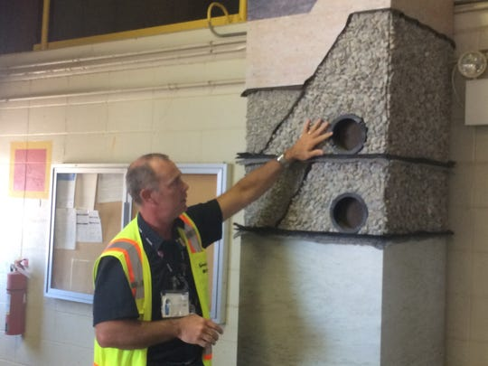 During a site tour in August, Frank Miller, project director for the on-site waste disposal facility, talks about the different layers and safeguards that would make up the cell's liner.