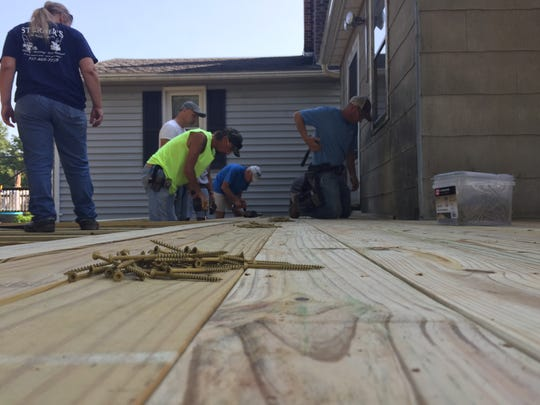 On Saturday a group of volunteers help put together a deck that will be part of a scooter ramp for Vietnam Marine veteran Jack Groft.